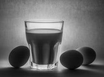 Melk in een glaskruik en eieren Stock Fotografie
