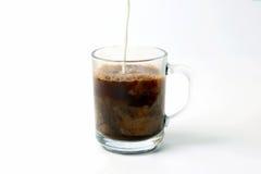 Melk in een transparante kop van zwarte koffie wordt gegoten die Stock Fotografie