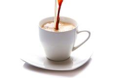Melk en koffie die in een kop wordt gegoten Stock Afbeelding