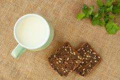 Melk in groene kop op linnenachtergrond met stukkenbrood Stock Afbeeldingen