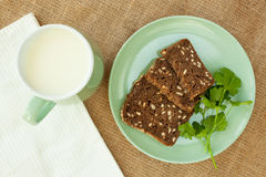 Melk in groene kop op linnenachtergrond met stukkenbrood Stock Foto