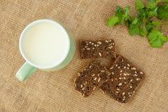Melk in groene kop op linnenachtergrond met stukkenbrood Royalty-vrije Stock Foto's