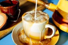 Melk het gieten in een koude kop van bevroren koffie stock afbeelding