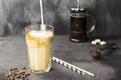 Melk het gieten in ijskoffie in een lang glas op een donkere achtergrond De ruimte van het exemplaar De achtergrond van het voeds Stock Foto's