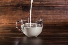 Melk het gieten in kop stock foto