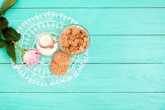 Melk, koekje, havervlokken Het ontbijt en roze nam op blauw houten servet toe als achtergrond en kant Hoogste mening en exemplaar Stock Foto