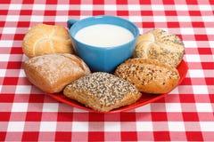 Melk in kop en diverse broodjes Stock Afbeeldingen