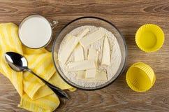 Melk, lepel op servet, bloemmengsel met stukken van boter voor muffins in kom, siliconevormen op lijst Hoogste mening royalty-vrije stock foto's