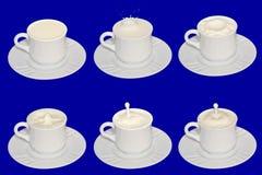 Melk in witte koppen op een blauwe achtergrond Stock Afbeeldingen