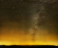 Melkachtige manier over zwarte bergen en stadslichten Stock Afbeelding