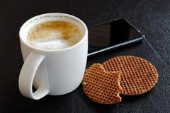Melkachtige schuimende koffie in witte die mok gedeeltelijk naast gedeeltelijk wordt gedronken stock foto's
