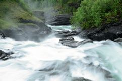 Melkachtige witte massieve lange waterval onderaan gladde valleirotsen en stenen in de zomer, lange blootstelling royalty-vrije stock afbeeldingen