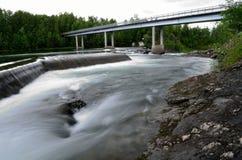 Melkachtige witte massieve lange waterval onderaan gladde valleirotsen en stenen in de zomer met autobrug Royalty-vrije Stock Fotografie