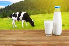 Melken Sie auf Tabelle mit Kuh auf dem Hintergrund Lizenzfreie Stockbilder