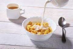 Melken Sie das Gießen in eine Schüssel von köstlichen Corn- Flakesgetreide und -kappe mit Espressokaffee Morgenfrühstück Stockfotografie
