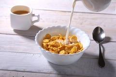 Melken Sie das Gießen in eine Schüssel von köstlichen Corn- Flakesgetreide und -kappe mit Espressokaffee Morgenfrühstück Lizenzfreies Stockbild