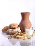 Melken Sie in einem transparenten Becher und in einem frischen Brot auf einem weißen Hintergrund Lizenzfreie Stockfotografie