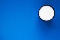 Melken Sie in einer Schale auf einer Draufsicht des blauen Hintergrundes stockbild