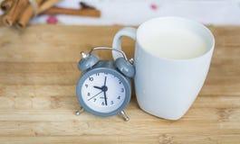 Melken Sie in einer weißen Schale mit kleiner Uhr auf einem hölzernen Hintergrund stockbilder
