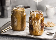 Melken Sie gegossen werden in ein Glas gefrorenen Kaffee Stockfoto