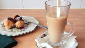 Melken Sie gegossen werden in einen schwarzen Kaffee stock video