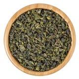 Melken Sie oolong grünen Tee in der hölzernen Schüssel, die auf weißem Hintergrund lokalisiert wird Stockfotos