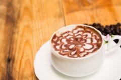 Melken Sie Schaumblumen-Kaffeetasse im Weiß auf einem Bretterboden Stockfoto