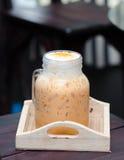 Melken Sie thailändischen Tee in den Glasbechern auf hölzerner Tabelle Stockbild