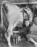 Melken von Zeit auf dem Bauernhof (alle dargestellten Personen sind nicht längeres lebendes und kein Zustand existiert Lieferante Stockfotos