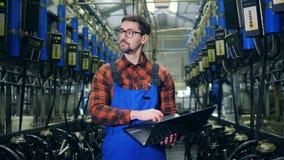 Melkende machines en een mannelijke deskundige die berekeningen op laptop maken stock footage