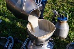 Melker gießen frische Milch des Filters zur Dose Lizenzfreie Stockfotos