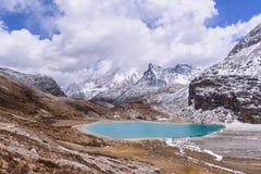 Melkmeer op de sneeuwbergen met wolken en hemel in Yading Royalty-vrije Stock Foto's