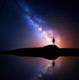 Melkweg en silhouet van een bevindende alleen mens stock foto