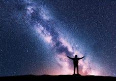 Melkweg en silhouet van een bevindende gelukkige mens stock foto's