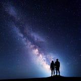 Melkweg met silhouet van mensen op de berg Stock Afbeeldingen