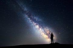 Melkweg Nachthemel en silhouet van een bevindende mens royalty-vrije stock afbeeldingen