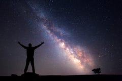 Melkweg Nachthemel en silhouet van een mens stock afbeeldingen