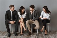 mellan skilda raser affärsfolk i formella kläder som har konversation, medan vänta arkivfoton