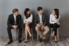 mellan skilda raser affärsfolk i formella kläder som har konversation tillsammans, medan vänta fotografering för bildbyråer