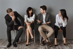 mellan skilda raser affärsfolk i formella kläder som har konversation tillsammans, medan vänta arkivbild