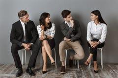 mellan skilda raser affärsfolk i formella kläder som har konversation tillsammans, medan vänta royaltyfri foto