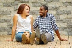 Mellan skilda raser charmiga par som bär tillfällig kläder som sitter på träyttersida som poserar för kameran som stirrar på de Royaltyfri Fotografi