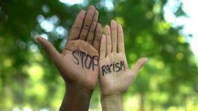 Mellan skilda raser folkhänder med stopprasismuttrycket, kamp mot diskriminering arkivfoton