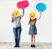 Mellan skilda raser kvinnor som rymmer en uttrycksfull emoticon, vänder mot förvånat och förbluffat socialt massmedia för ansikts arkivfoto