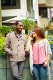 Mellan skilda raser lyckliga charmiga par som bär tillfällig kläder som påverkar varandra för kamera i stads- miljö för det fria Royaltyfria Bilder