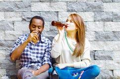 Mellan skilda raser par som bär tillfällig kläder som sitter in mot den gråa tegelstenväggen som tycker om några drinkar och varj Arkivfoto