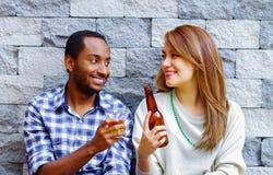 Mellan skilda raser par som bär tillfällig kläder som sitter in mot den gråa tegelstenväggen som tycker om några drinkar och varj Arkivfoton