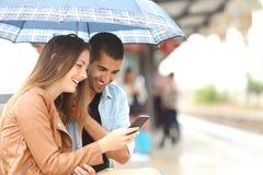 Mellan skilda raser par som delar en telefon i en drevstation arkivbild
