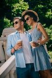 mellan skilda raser stilfulla par i solglasögon med legitimationshandlingarkoppar kaffe arkivfoto