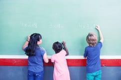 Mellan skilda raser studenter som skriver nummer på den svart tavlan på elementärt royaltyfria bilder